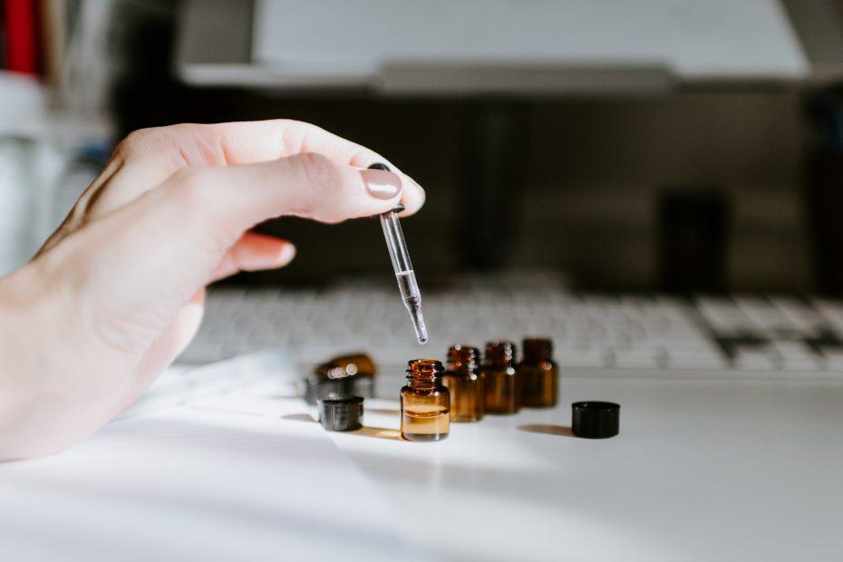 Kleine Ölfläschchen auf einem Schreibtisch vor Tastatur