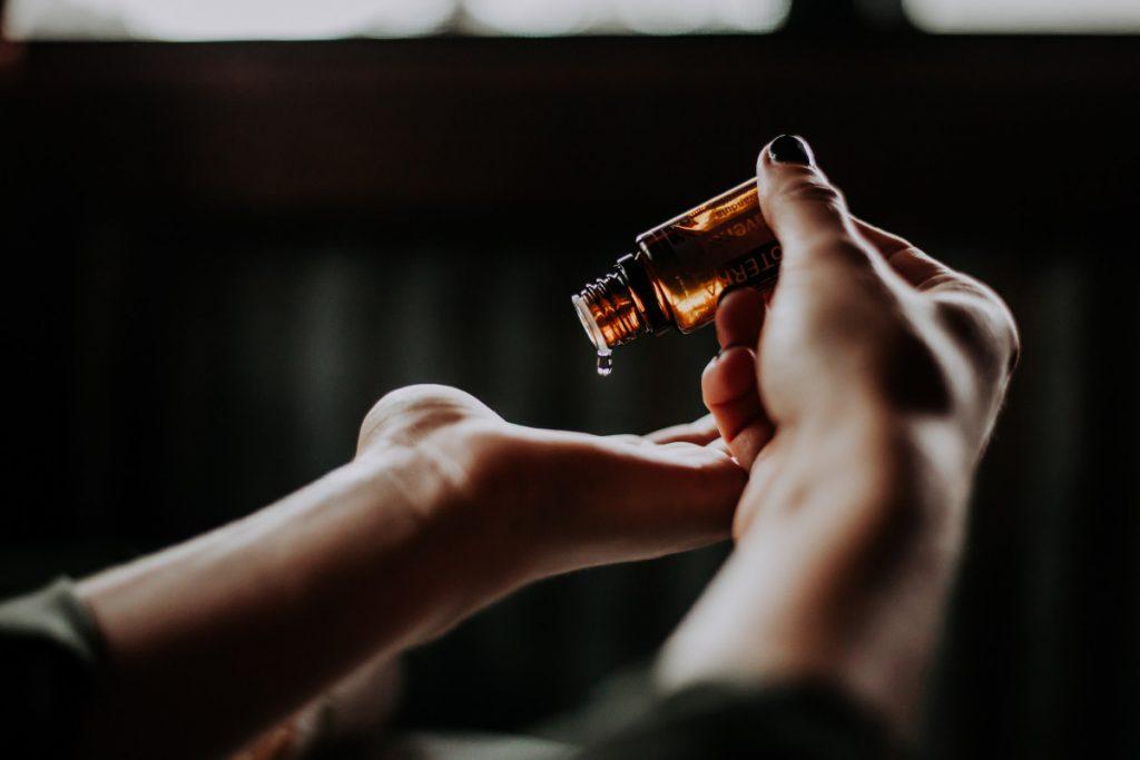 Öl wird in eine Hand getropft