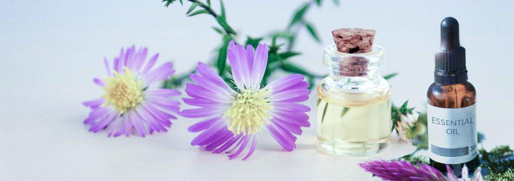 Blume mit zwei Flaschen ätherischem Öl