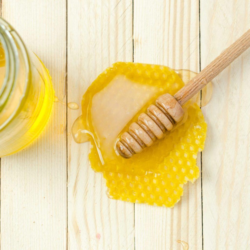 Honig mit Wabe auf einem Holztisch