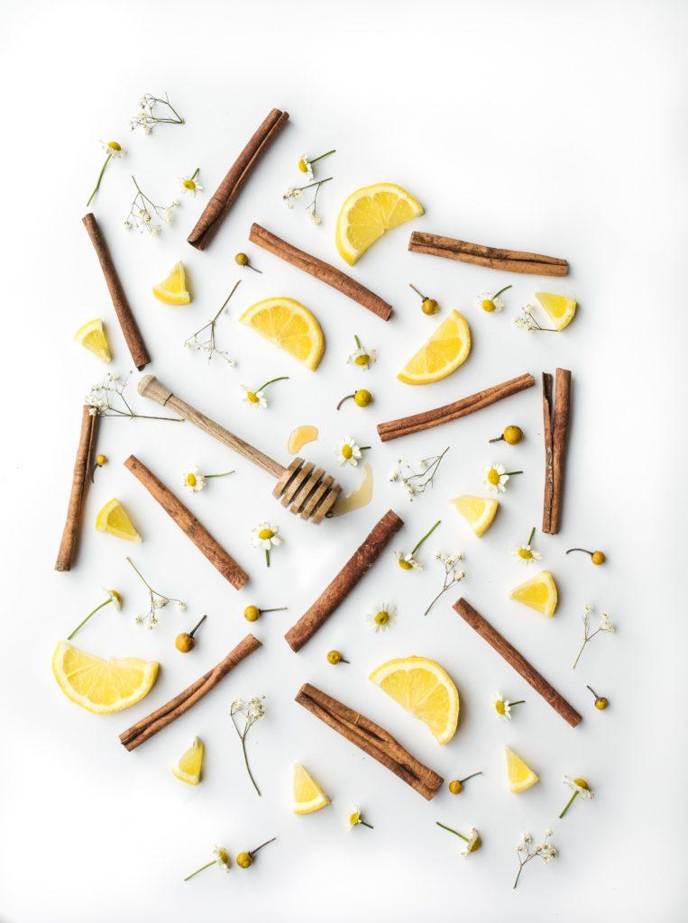 Honig, Zitronenscheiben, Zimtrollen und Gänseblumenblüten, nett arrangiert