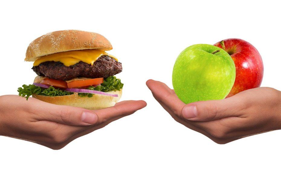 Eine Hand mit Burger, eine mit Äpfeln
