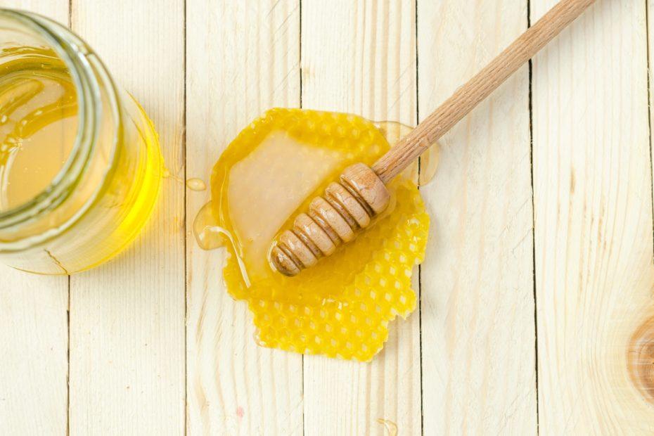 Honig mit Mittelwand auf hellen Holzbrettern